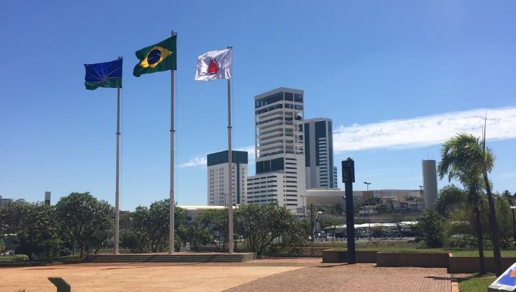 Fotografia de Uberlândia contendo a bandeira do Brasil, de Minas e de Uberlândia. Ao fundo o complexo do Center Shopping.